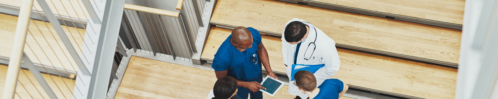 Medical team having an emergency discussion standing grouped in a stairwell at the hospital looking up information on a tablet