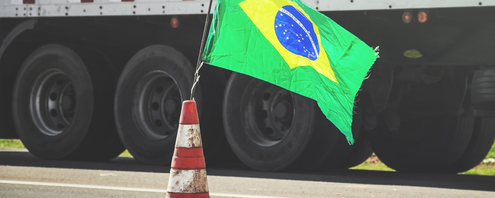 Brazilian flag on a red traffic cone of a highway with a blurred truck on background