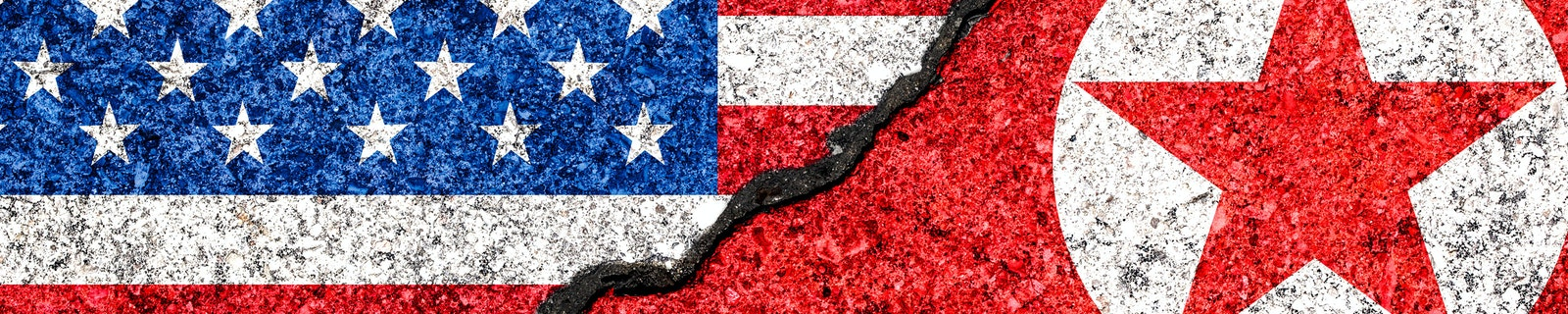 Flags of North Korea and USA painted on cracked wall background