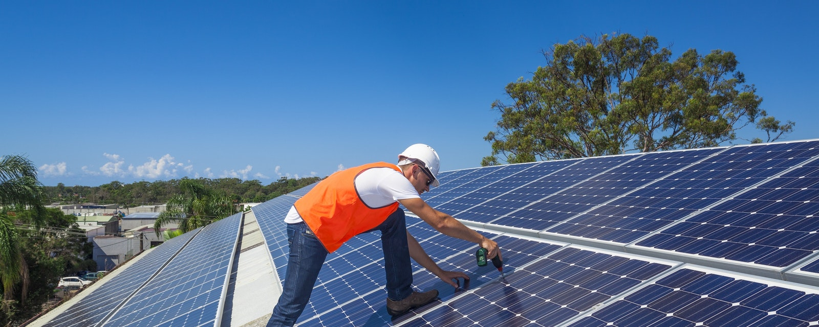 Young,Technician,Installing,Solar,Panels,On,Factory,Roof